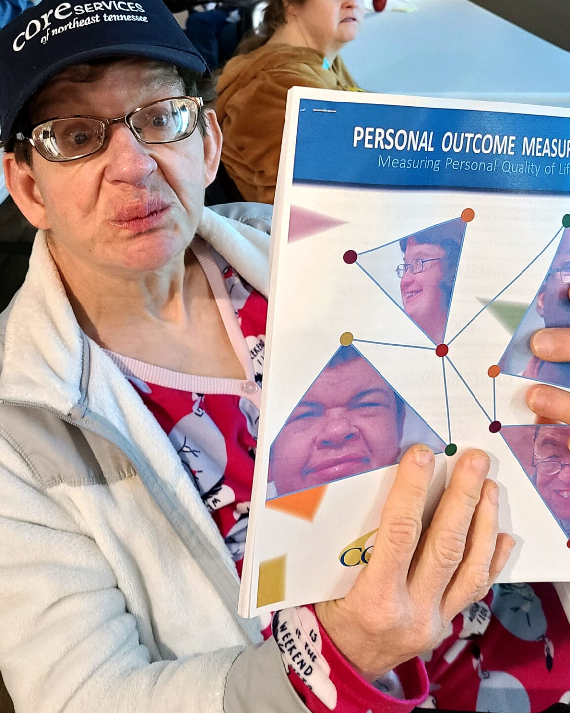 Person receiving services through Core Services holds up Personal Outcome Measures® Manual