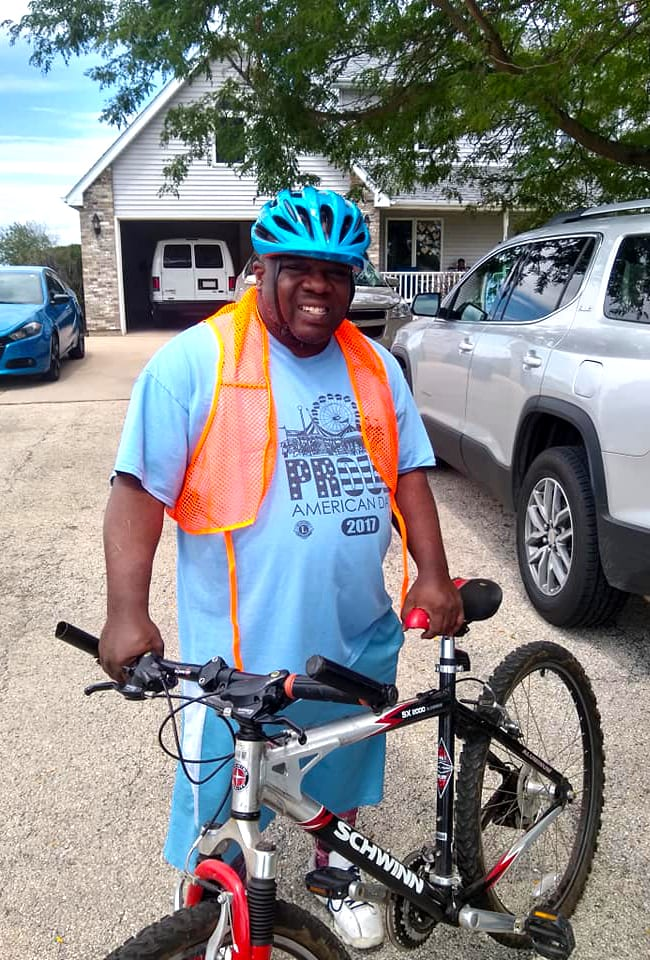 Man wearing helmet and vest standing with his bicycle