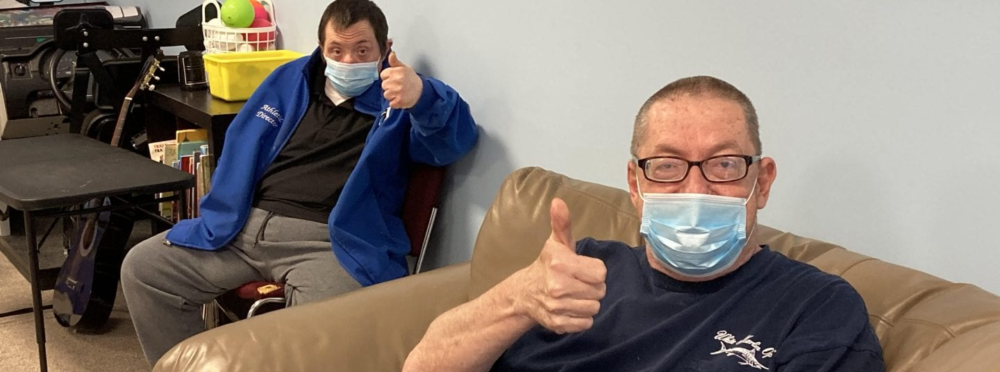 Two men wearing masks and sitting down while holding their 'thumbs up'