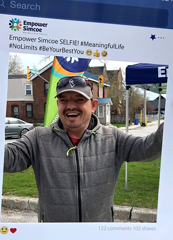Person stands outdoors holding a 'selfie sign' of a Facebook frame